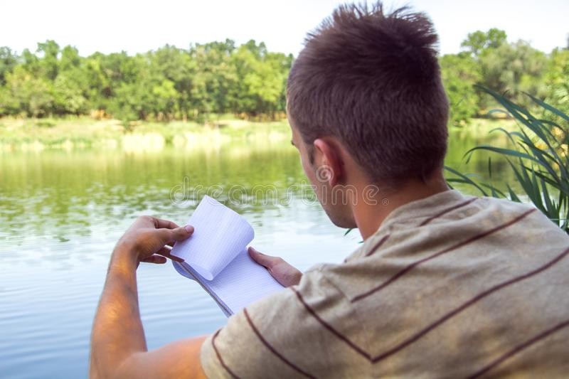 Notebook of a young man, a man close to the lake, painting landscape in Notepad. Summer Sunny day. to turn the page royalty free stock photo
