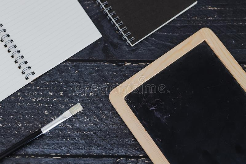 Notebooks and brush on wooden desk with copyspace to add you text. Concept of artist and inspiration royalty free stock photography