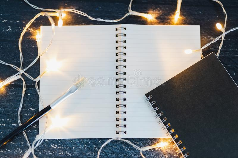 Notebooks and brush on wooden desk with copyspace to add you textsurrounded by fairy lights. Notebooks and brush on wooden desk with copyspace to add you text stock photo