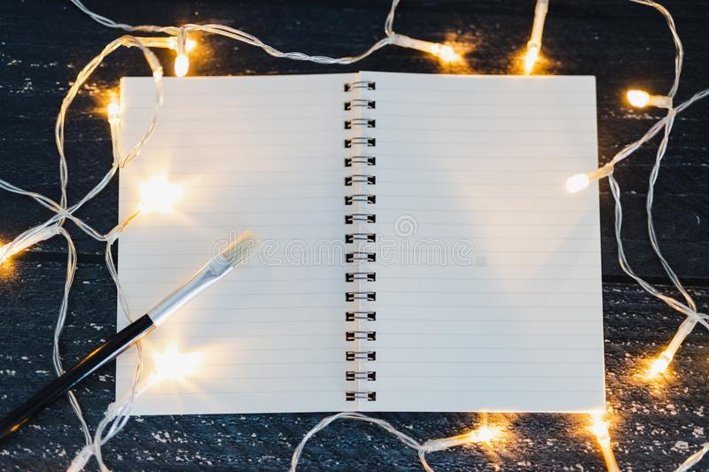 Notebooks and brush on wooden desk with copyspace to add you textsurrounded by fairy lights. Notebooks and brush on wooden desk with copyspace to add you text royalty free stock image