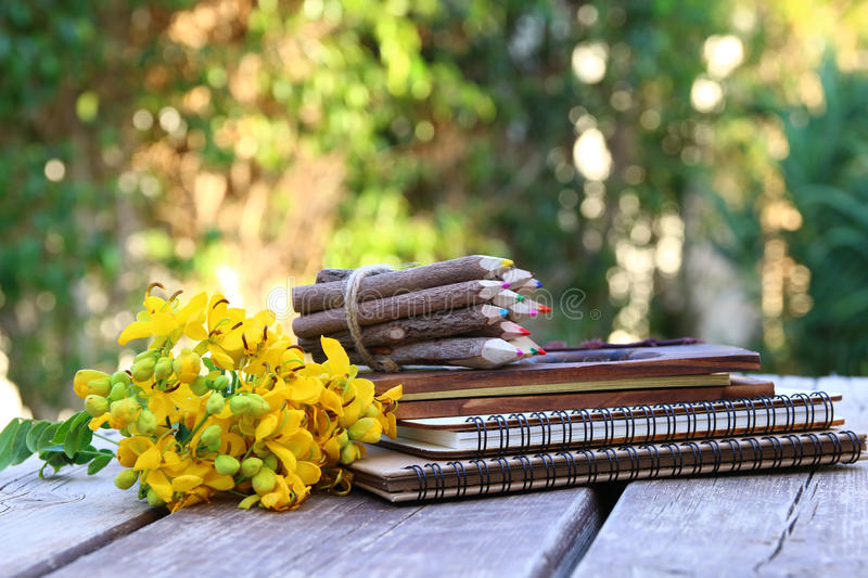 notebooks, colorful pencils on wooden table outdoors royalty free stock image