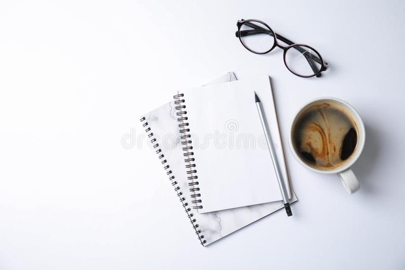 Notebooks with glasses and coffee on white background, top view. Space for text stock photo