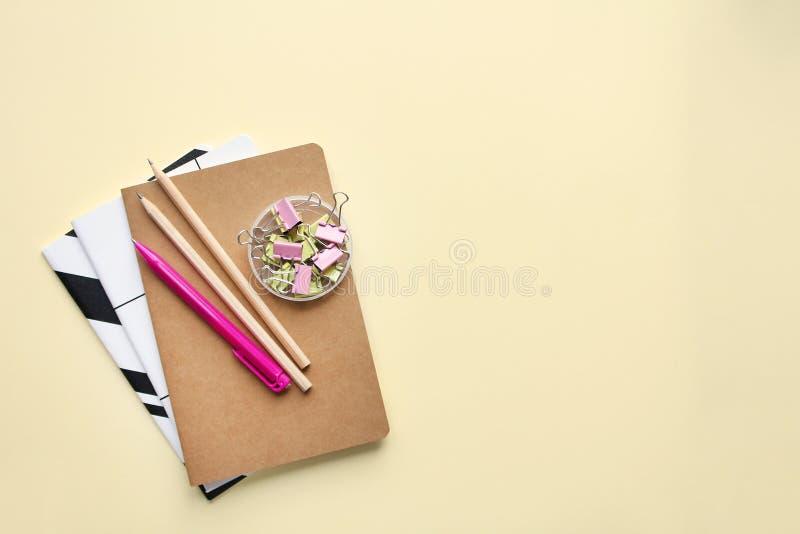 Notebooks, pencils, pen, binders on biege background. stock photos