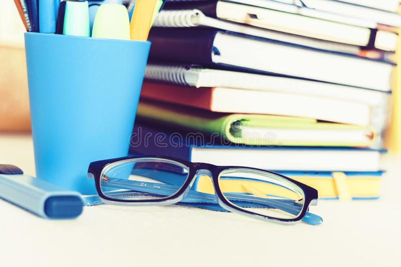 Notebooks piles, stack of books education back to school background, textbooks, glasses and pencils in plastic holder with copy royalty free stock images