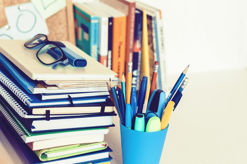 Notebooks piles, stack of books education back to school background, textbooks, glasses and pencils in plastic holder with copy stock images