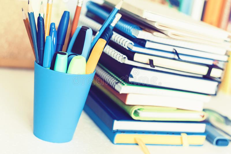 Notebooks piles, stack of books education back to school background, textbooks, glasses and pencils in plastic holder with copy royalty free stock photography