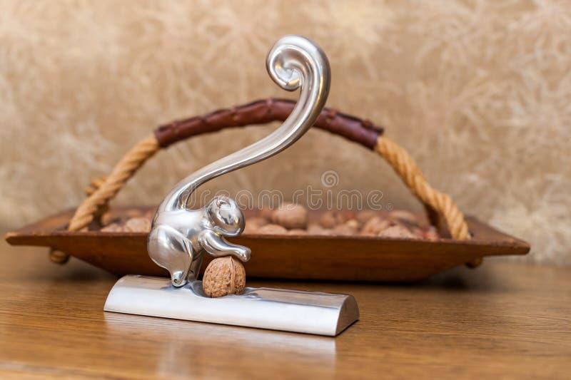 Notekraker en houten mand met noten stock afbeeldingen