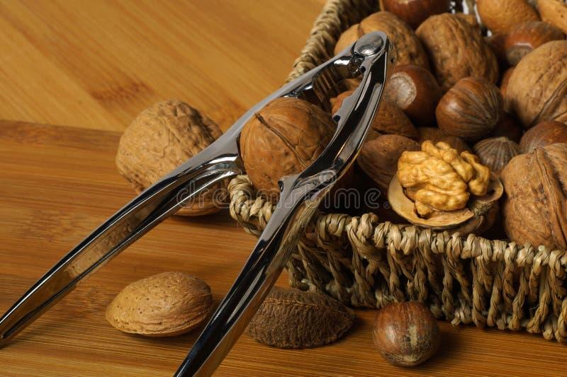 Notekraker op de mand wordt gebaseerd die Gevlechte die mand met noten wordt gevuld: okkernoten, Braziliaan, hazelnoten en amande royalty-vrije stock afbeelding