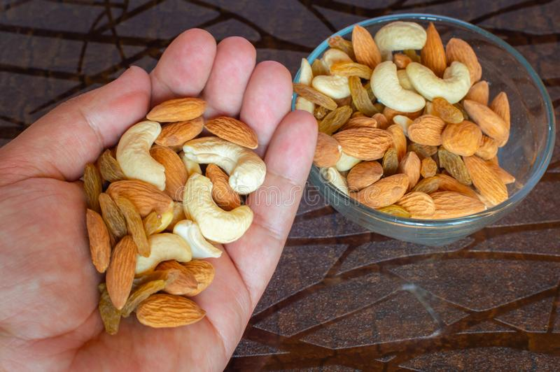 Noten in de noten van de palmhand in rozijnen van de cachouamandelen van de kom de bruine lijst stock foto's