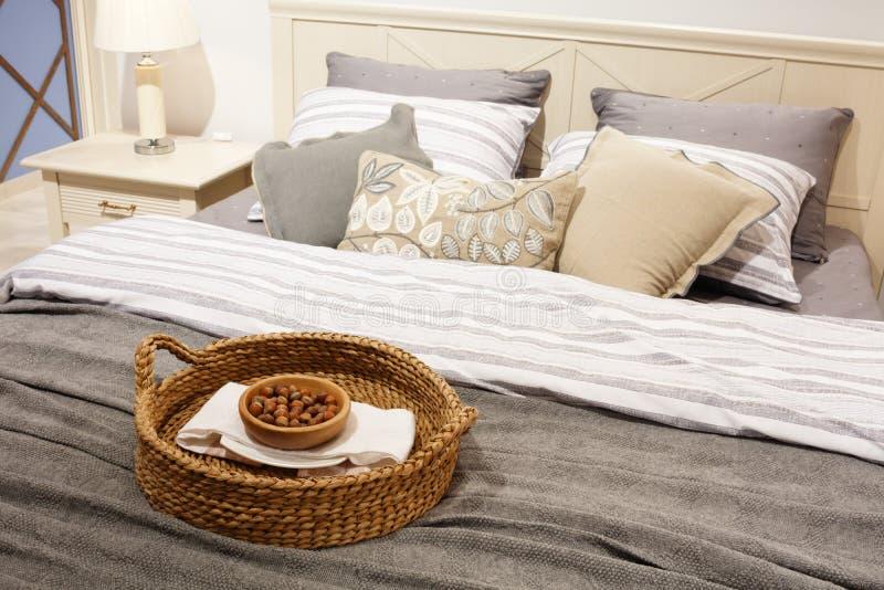 Noten in een rieten mand op het bed, een gift voor gasten slaapkamer van de luxe de moderne stijl in grijze en blauwe tonen, Binn stock foto