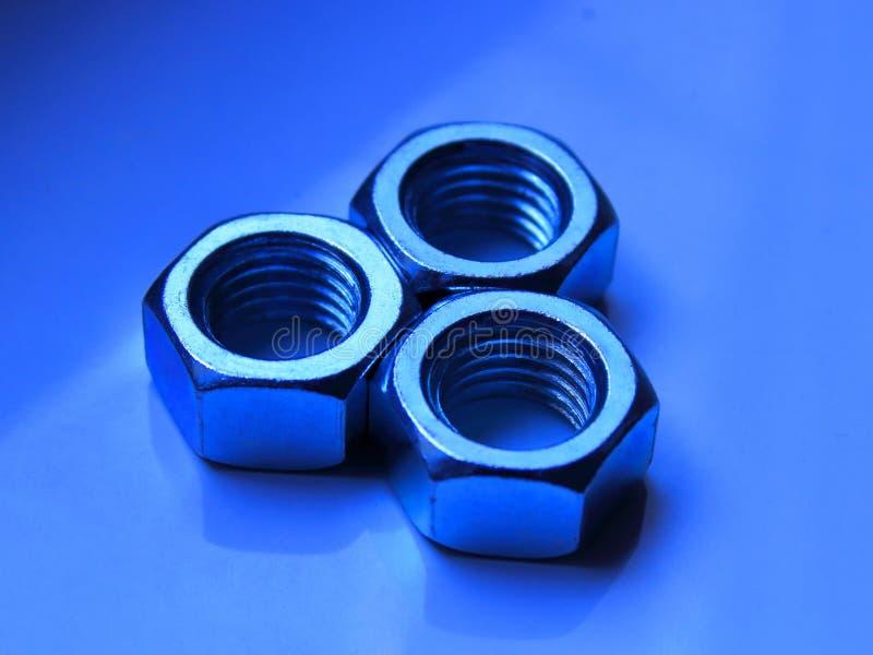 Noten - en - bouten op blauw en purper stock afbeelding