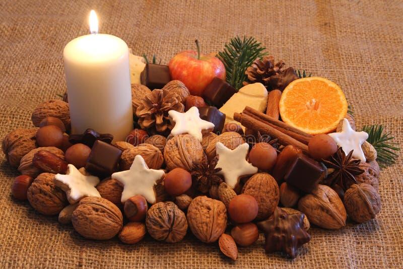 Noten, snoepjes, vruchten, bisquits en witte kaars royalty-vrije stock afbeeldingen