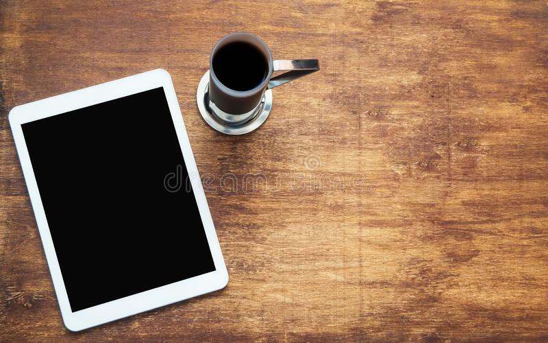 Notentablette und -Tasse Kaffee auf hölzernem Schreibtisch Schwarze Leerstelle auf dem Schirm Spott oben lizenzfreies stockfoto