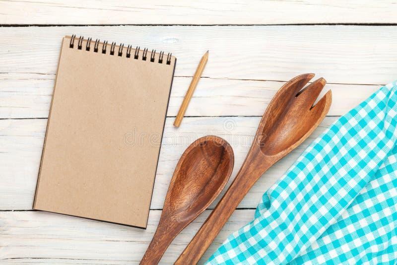 Notepad över kökshandduken och redskap på trätabellen royaltyfria foton