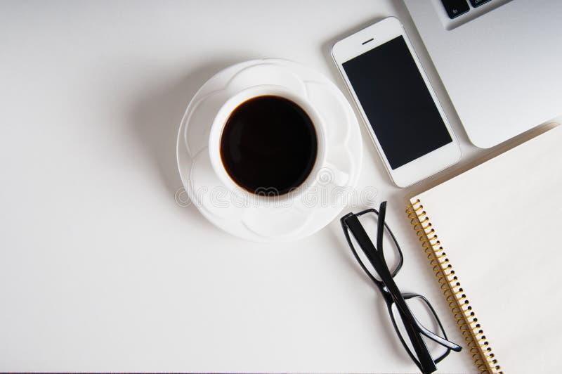 Notepad-, bärbar dator- och kaffekopp på den wood tabellen arkivfoton