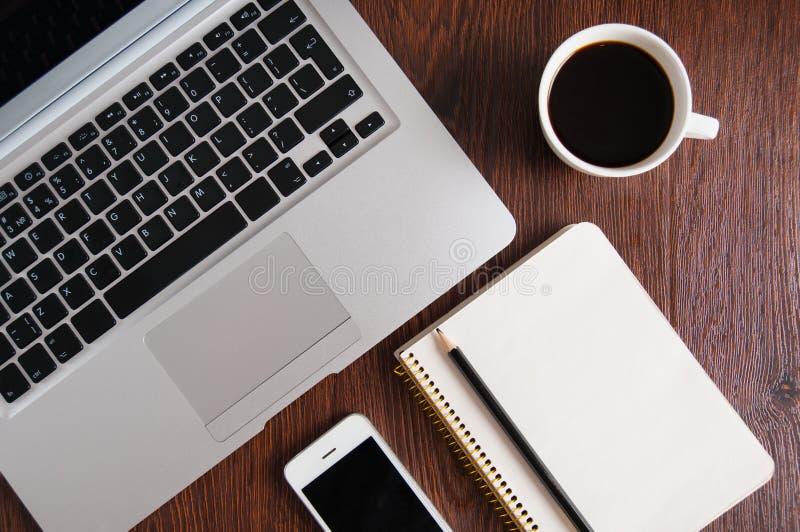 Notepad-, bärbar dator- och kaffekopp på den wood tabellen royaltyfria bilder