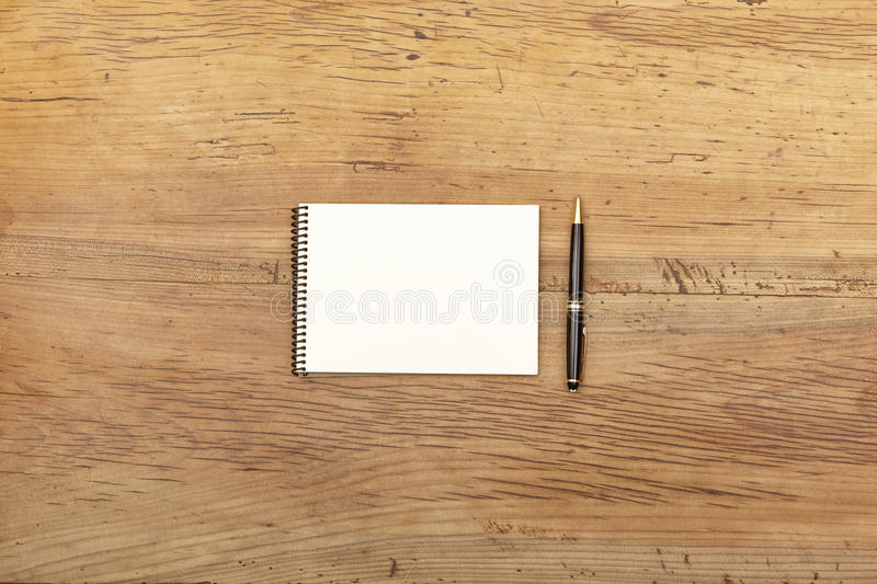 Notepad and ballpen on wood royalty free stock images