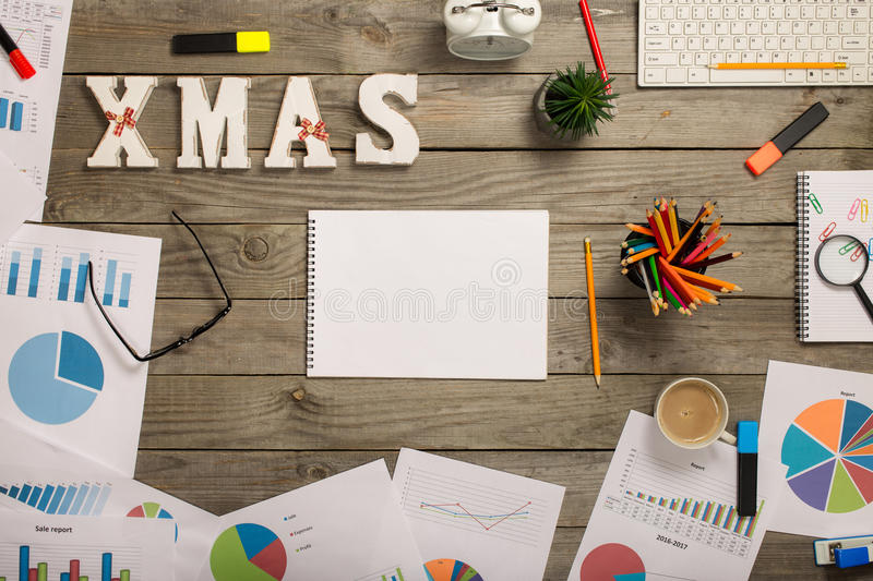 Notepad with blank pages with office objects and word xmas. Notepad with blank pages on wooden office desk with office objects and word xmas, top view royalty free stock images