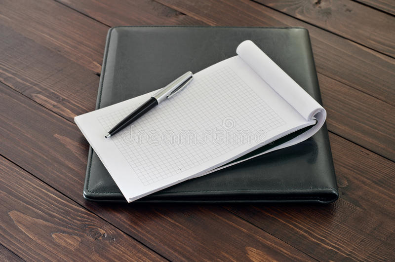 Notepad with blank pages. With a pen on the leather business folder on the office table close up. Top view. Copy space royalty free stock photos