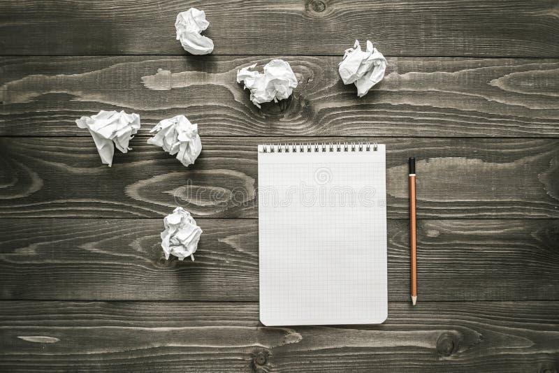 Notepad, blyertspenna och skrynkligt papper på kontorsskrivbordet, lekmanna- lägenhet, idérikt begrepp för affär arkivbild
