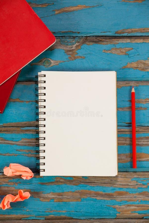 Notepad, blyertspenna, röda böcker och skrynkligt papper arkivfoto