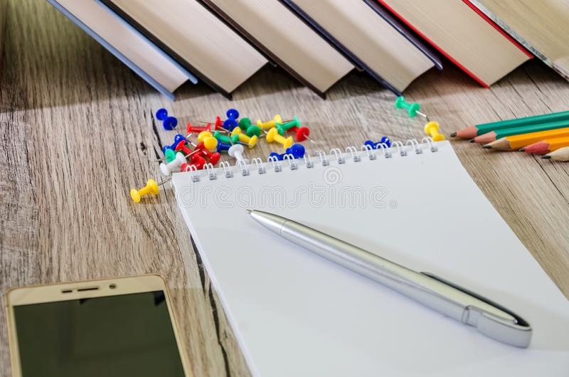 Notepad with books and pencils on the table. Dollars, calculator and smartphone. Office concept. stock images