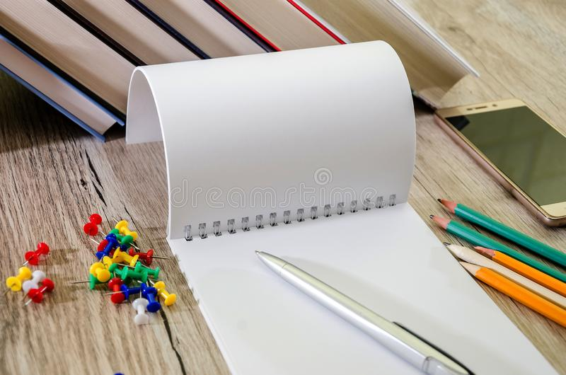 Notepad with books and pencils on the table. Dollars, calculator and smartphone. Office concept. royalty free stock images