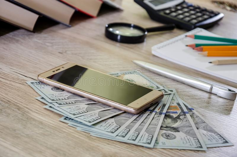 Notepad with books and pencils on the table. Dollars, calculator and smartphone. Office concept. royalty free stock photo