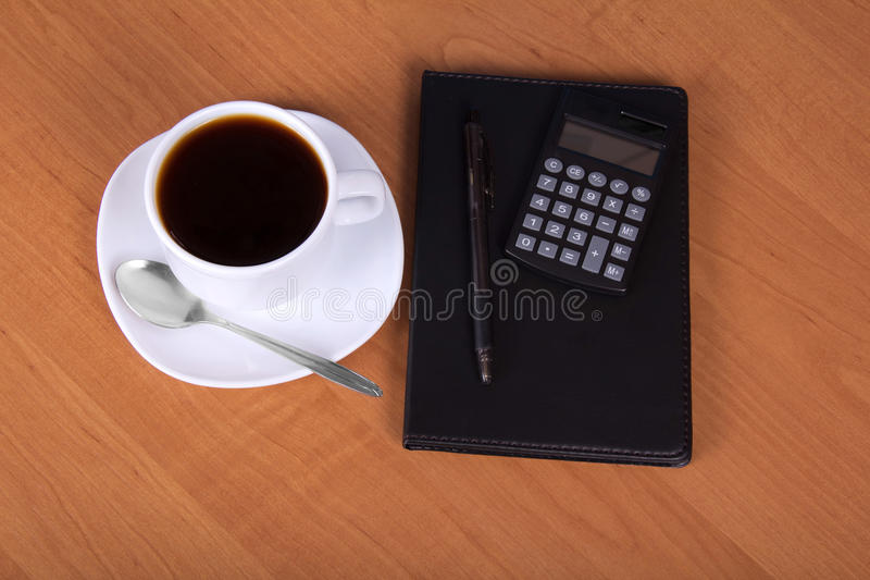 Notepad, calculator and cup of coffee on wood stock image
