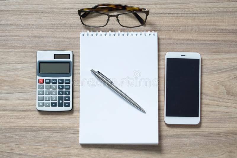 Notepad, calculator, smartphone, glasses and sliver ballpen. Notepad, calculator, smartphone, glasses and sliver ballpen on wooden office desk. Image with copy stock photography