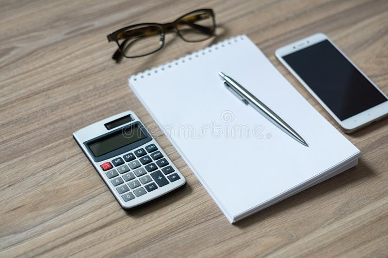 Notepad, calculator, smartphone, glasses and sliver ballpen. On wooden office desk. Image with copy space. Selective focus royalty free stock photo
