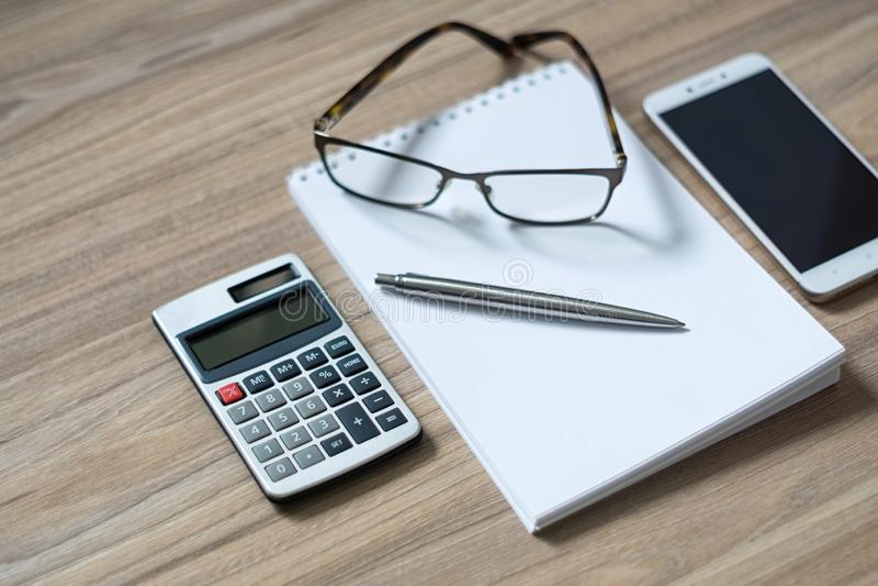 Notepad, calculator, smartphone, glasses and sliver ballpen. On wooden office desk. Selective focus stock image