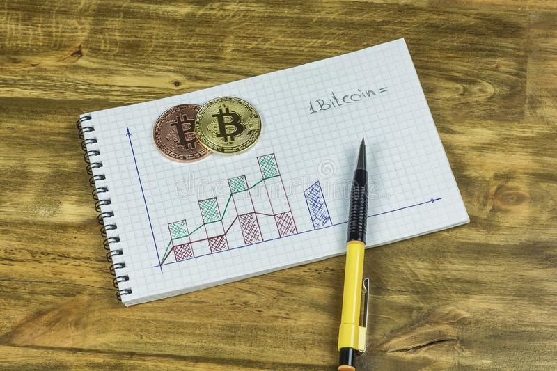 Notepad with chart, gold and platinum Bitcoin coins. On the notebook with the chart is a pen, gold and platinum coins Bitcoin royalty free stock images