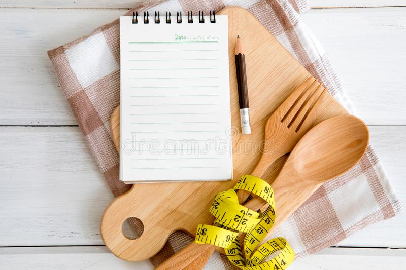 Notepad on chopping board with a wooden fork and spoon and meas. Notepad on chopping board with wooden fork and spoon and measuring tape on white table , recipes royalty free stock photo