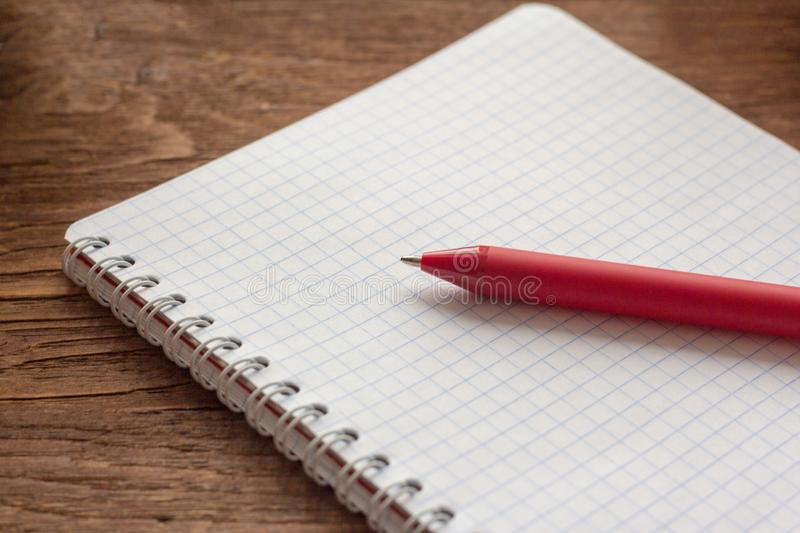 Notepad with clean sheet for writing and red pen on wooden table royalty free stock photos