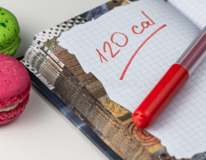 Notepad com Cálculo de Calorias e Dois Desserts Macaroon imagens de stock royalty free