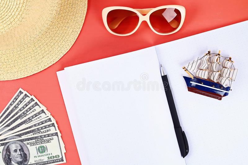 Notepad coral background, sun glasses, hat, money. Top view, copy space. Summer background, travel. Blank notepad on a coral background, sun glasses, hat, money royalty free stock photo