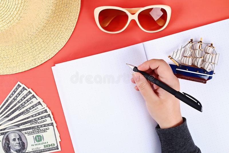 Notepad coral background, sun glasses, hat, money. Top view, copy space. Summer background, travel. Blank notepad on a coral background, sun glasses, hat, money royalty free stock images