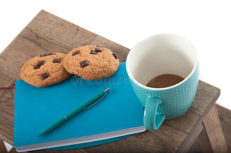 Notepad, cup, pen in turquoise color with chocolate chip cookies. wooden table and white background. Great morning and start of th royalty free stock images