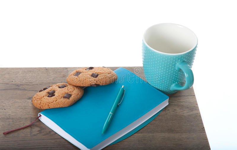 Notepad, cup, pen in turquoise color with chocolate chip cookies. wooden table and white background. Great morning and start of th royalty free stock photo