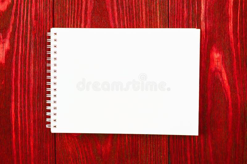 Notepad de escritório branco está sobre um fundo vermelho brilhante de madeira, design minimalista, vista superior, apresentação  imagens de stock royalty free