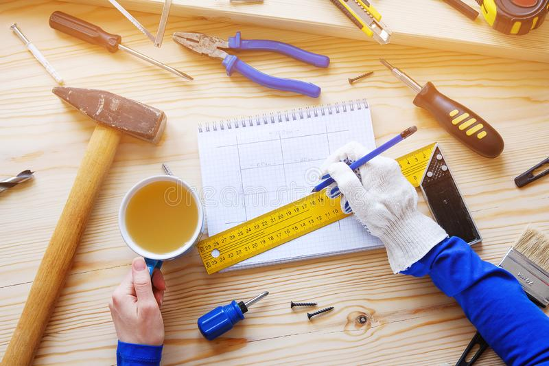 Notepad with drawings and construction tools. In the hands of women Brigadier mug of tea and a pencil, a break in the workplace. royalty free stock images