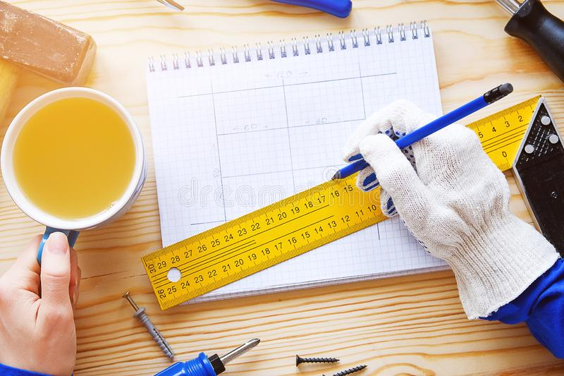 Notepad with drawings and construction tools. In the hands of women Brigadier mug of tea and a pencil, a break in the workplace. royalty free stock photo