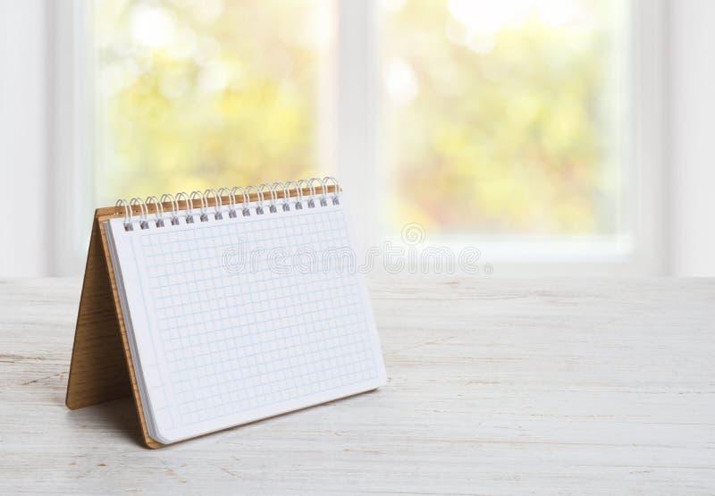 Notepad eller kalender på trätabellen över suddig fönsterbakgrund royaltyfri fotografi