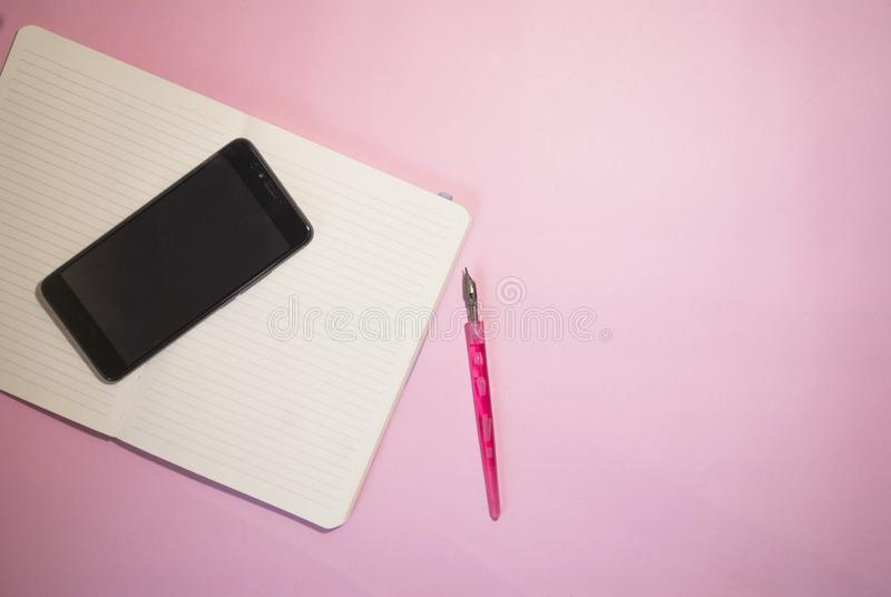 Notepad with empty place for text and phone on a pink background stock images