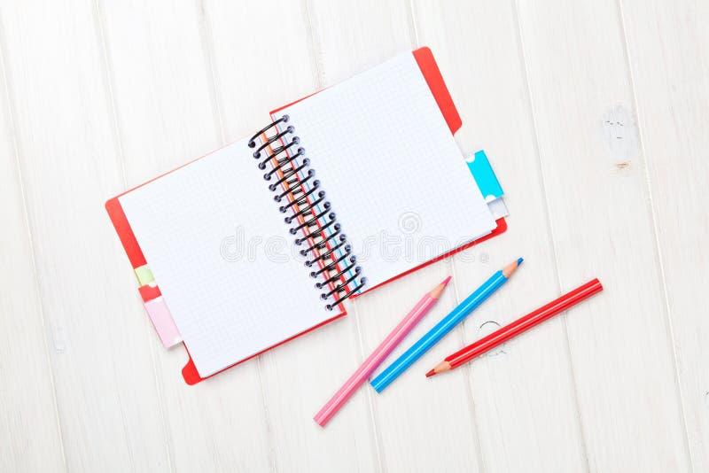 Notepad för Whtie trätabellmellanrum och färgrika blyertspennor arkivbild