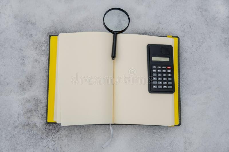 Notepad, förstoringsapparat och en räknemaskin på en vit bakgrund arkivfoto