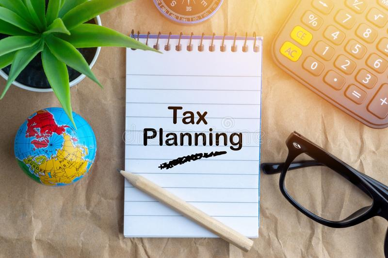 Notepad, flower vase, spectacle, pencil , compass, globe, calculator and words TAX PLANNING. On wooden paper background. Business and education concept royalty free stock photography