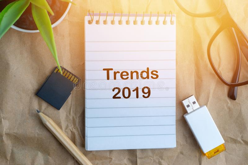 Words TRENDS 2019 on wooden paper background. Business and education concept. Notepad, flower vase, spectacle, storage card, pencil and words TRENDS 2019 on royalty free stock photo