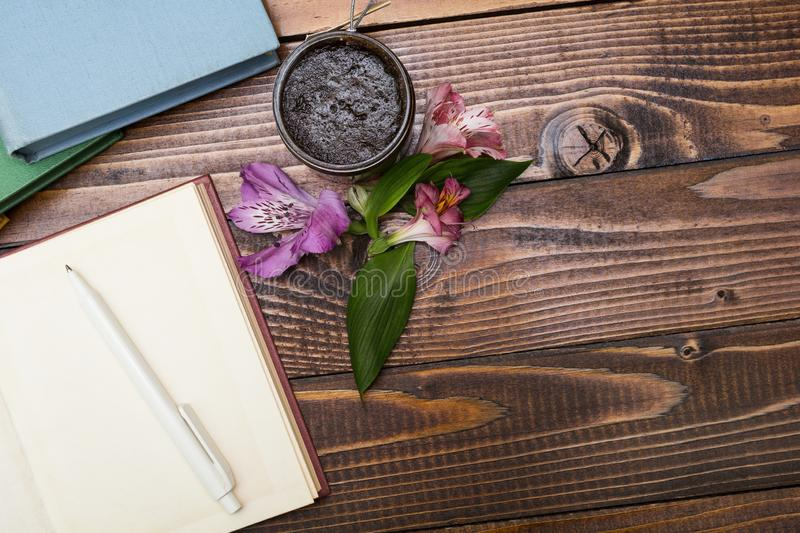 Notepad, flowers and scrub on a wooden table royalty free stock images